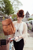 Young Woman Putting her Bag on a Bicycle Basket Royalty Free Stock Photography