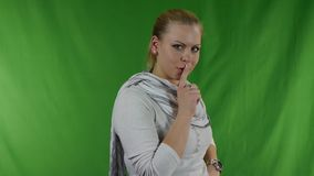 Young woman putting her finger to her lips for shh gesture stock video