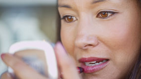 Young woman putting her lipstick on Stock Photography