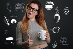 Young woman putting her thumb up while enjoying her morning coffee. Good morning. Emotional young energetic woman winking and putting her thumb up while standing stock photos