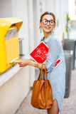 Woman using old mailbox outdoors Stock Image