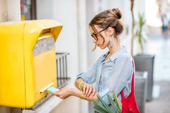 Woman using old mailbox outdoors Royalty Free Stock Image