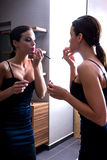 Young woman putting on lipstick in front of a mirror Stock Photo