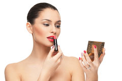 Young woman putting lipstick on lips Royalty Free Stock Photography