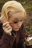 Young woman putting on make-up outdoors Royalty Free Stock Image