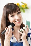 Young Woman Putting On Make Up At Home Stock Photography