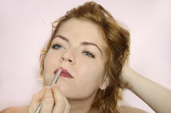 Young woman putting on makeup Royalty Free Stock Photography