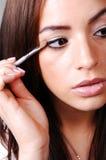 Young woman putting makeup. Royalty Free Stock Photos