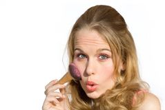Young woman putting on makeup Stock Photos
