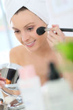 Young woman putting on makeup Royalty Free Stock Images