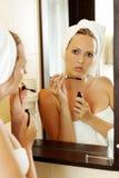 Young woman putting mascara on Stock Photos
