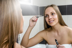 Young woman putting on mascara Royalty Free Stock Images