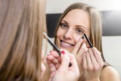 Young woman putting on mascara Stock Photo