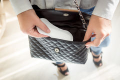 Young woman putting menstrual pad out of handbag Stock Photography