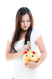 Young Woman Putting Money Into Piggy Bank Royalty Free Stock Photos