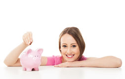 Young woman putting money in piggy bank Stock Photography