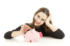 Young woman putting money into piggybank Royalty Free Stock Photography