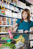 Young woman putting a packet in a shopping trolley Royalty Free Stock Images