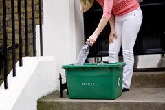 A young woman putting a plastic bottle in a recycling box Stock Photos
