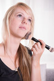Young woman putting powder with a brush on her face Royalty Free Stock Images