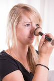 Young woman putting powder with a brush on her nose Stock Image