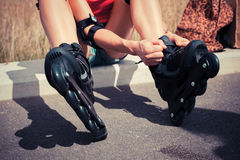Young woman putting on rollerskates Royalty Free Stock Images