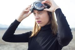 Young woman putting on sand goggles in desert Royalty Free Stock Photos