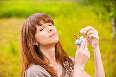 Young woman putting scent on. Portrait of young pleasant woman putting scent on herself at summer green park stock photography