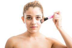 Young woman putting some makeup on. Portrait of an attractive young woman with bare shoulders putting some blush on her face with a makeup brush Stock Image
