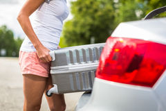 Young woman putting a suitcase into her car's trunk Royalty Free Stock Image