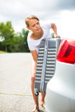 Young woman putting a suitcase into her car's trunk Royalty Free Stock Photography