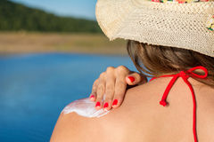 Young woman putting sun lotion on summer vacation Stock Photos