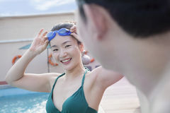 Young woman putting on swimming goggles and looking at man by the pool Royalty Free Stock Photos