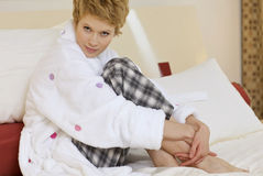 Young woman in pyjamas sitting on bed Stock Photography