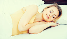 Young woman in pyjamas sleeping in bed Royalty Free Stock Images