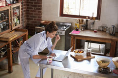 Young woman in pyjamas using laptop at breakfast, high angle Royalty Free Stock Photography