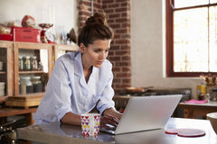 Young woman in pyjamas using laptop in kitchen, close up Royalty Free Stock Photos