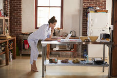 Young woman in pyjamas using laptop in kitchen, full length Stock Photography