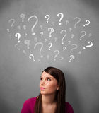 Young woman with question marks above her head Royalty Free Stock Images
