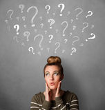 Young woman with question marks above her head Stock Image
