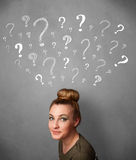 Young woman with question marks above her head Royalty Free Stock Photos