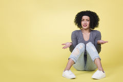 Young woman with questioning look isolated on yellow background. Stock Images