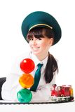 Young woman, railroad dispatcher. With traffic light and toy locomotive royalty free stock images