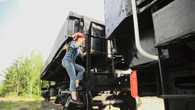 A young woman railroader get down the stairs and walking next to train. A young woman railway worker in an orange helmet get down the stairs from the cargo stock footage