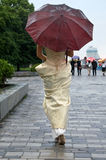 Young woman in the rain. Girl in a beautiful dress comes under the umbrella Stock Photo