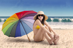 Young woman with rainbow umbrella at beach Stock Photo