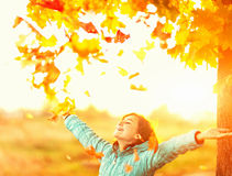 Young woman with raised arms below autumn tree with falling leaves Stock Photography