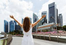Young woman with raised arms on skyscrapers background. Young woman with raised arms to the sky enjoying the sun and beautiful cityscape in downtown of Singapore royalty free stock photo