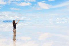 Young woman with raised arms. Young woman standing on Salar de Uyuni with raised hands Royalty Free Stock Photo