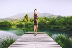 Young woman with raised arms up on the nature background. Young woman stands on a wooden bridge with raised arms up on the nature background. Travel, Freedom Royalty Free Stock Image